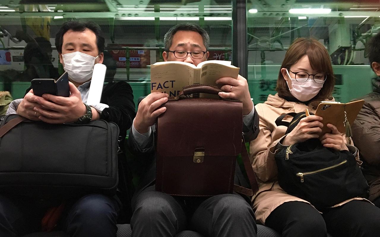 foto a colori scatta sulla metropolitana di Tokyo. ritrete tre persone sedute vicine. quella centrare legge un libro ed è senza mascherina ed è il più anziano dei tre, le altre due laterali sono entrambi con la mascherina e hanno in mano il cellulare. simbolo del divario generazionale