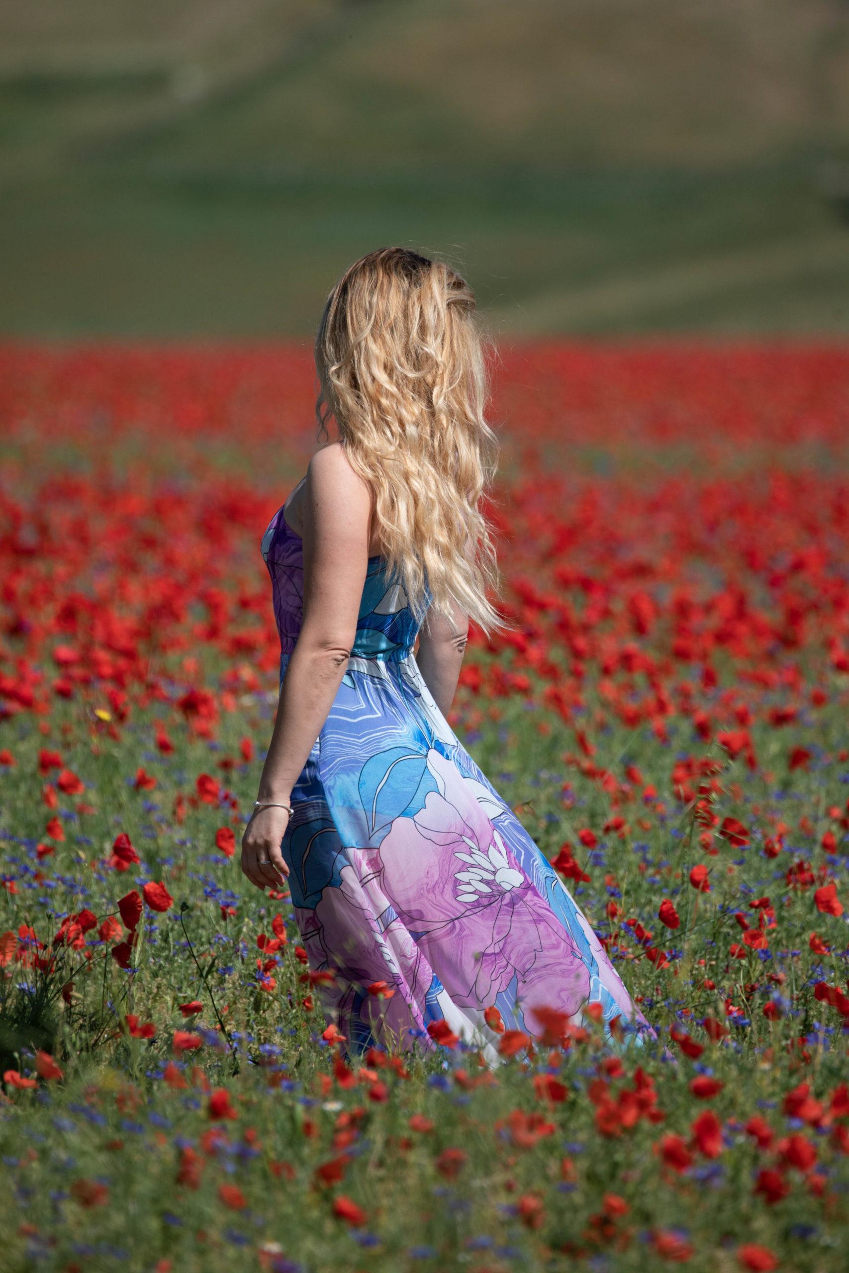 Ragazza con vestito lungo colorato ritratta in un campo di papaveri